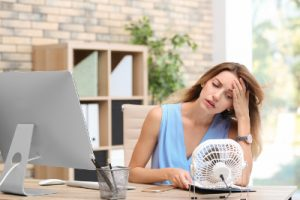 woman in office hot with not air conditioning